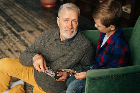 Top view of handsome bearded gray-haired grandfather showing photo to his grandson, enjoy memories watching family photo album sitting on armchair and floor at home in cozy room, looking at the camera