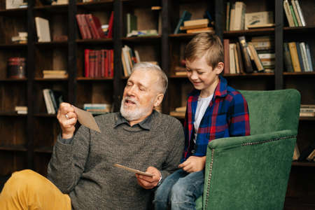Senior bearded gray-haired grandfather with his grandson enjoy memories watching family photo album sitting on armchair and floor at home in living room with an authentic aristocratic interior.