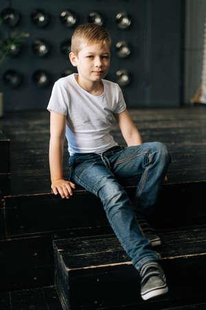 Portrait of handsome confident child boy sitting on dark floor posing in photo studio. Adorable Caucasian schoolboy kid posing indoor, looking at the camera. Archivio Fotografico