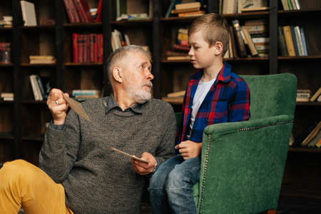Handsome bearded gray-haired grandfather with his cute grandson having fun looking at an old photo album, enjoying memories watching family photo album at home in living room background on bookshelves Archivio Fotografico