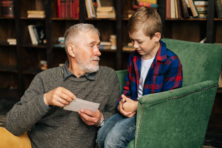 Portrait of happy bearded grandpa talking with cute grandson, having fun looking at an old photo album, enjoying memories watching family photo album at home in cozy room background on bookshelves