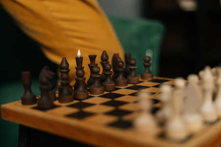 Side view of chessboard with placed chess pieces on black old vintage table, focus on background. End of preparation for an intellectual game in a warm home atmosphere.