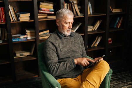 Focused bearded gray-haired mature adult male using digital tablet , sitting at home on background of bookshelves in cozy living room with authentic aristocratic interior.