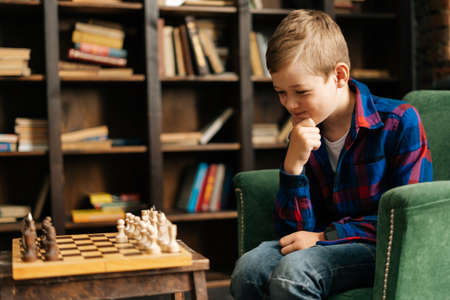 Portrait of smart little boy playing chess sitting at home in dark living room. Thoughtful small pre-school kid thinking about next move sitting over the chessboard