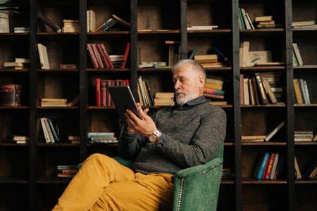 Side view of serious bearded gray-haired mature adult male communicating by digital tablet, sitting at home on background of bookshelves in cozy room with an authentic aristocratic interior.