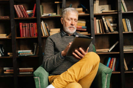 Handsome mature adult man typing online message using digital tablet, sitting at home on background of bookshelves in cozy dark room with an authentic aristocratic interior.