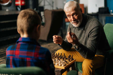 Mature adult bearded gray-haired grandfather explaining rules of chess game to grandchild at home in cozy living room with an authentic aristocratic interior.