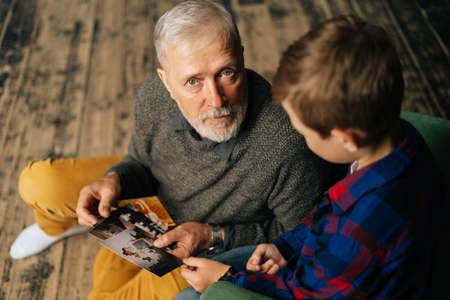 Top view of handsome bearded gray-haired grandfather with his grandson having fun looking at an old photo album, enjoying memories watching family photo album at home in living room