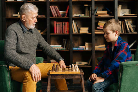 Senior grandfather and grandson are playing chess sitting at desk in cozy dark living room with an authentic aristocratic interior. Different generations of family spend time together.