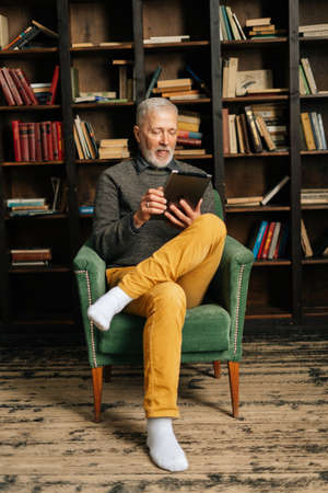 Happy smiling mature adult male typing online message using digital tablet, sitting at home on background of bookshelves in cozy dark room with an authentic aristocratic interior. Archivio Fotografico
