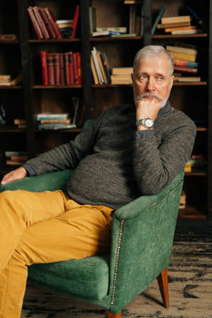 Portrait of thinking bearded gray-haired mature male, thoughtfully holding fist hand near chin, sitting at home on background of bookshelves in cozy dark room with an authentic aristocratic interior.