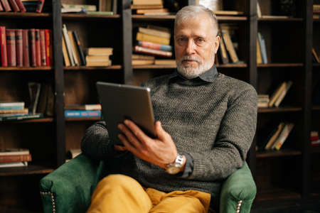 Portrait of confident bearded gray-haired mature adult male holding digital tablet in hand sitting at chair at home on background of bookshelves in cozy room with an authentic aristocratic interior.