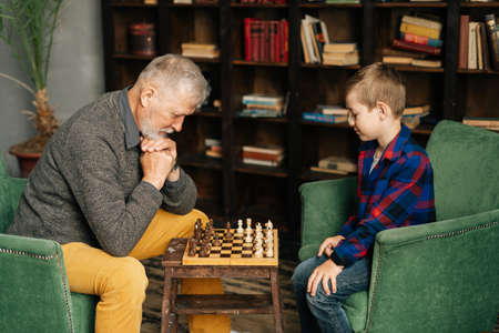 Thoughtful beard grandpa playing chess with grandson, thinking about next step in chess game sitting at chessboard in front of child. Grandchild playing chess with grandparent, leisure activity.