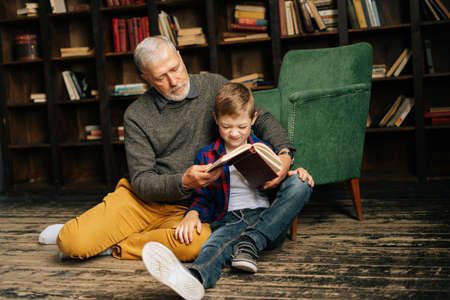 Senior grandfather and little grandson reading interesting book together sitting on floor on home library room. Bearded gray-haired grandpa reading book for grandson.