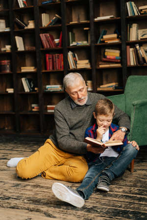 Happy old senior grandfather and little grandson reading interesting book together sitting on floor in home library room. Bearded gray-haired grandpa reading book for grandson.