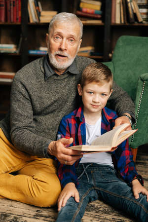 Portrait of happy child boy sitting with his grandfather and reading an interesting book together. Bearded gray-haired grandpa reading book for grandson. Grandparent telling fairytale for night. Archivio Fotografico