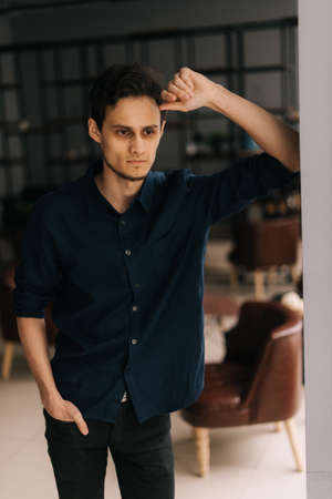 Serious handsome young business man with pensive expression standing near window in workplace. Confident guy posing at office room with modern interior, looking away. Archivio Fotografico