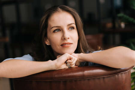 Close-up of face of pensive young woman sitting and leaning on the back of the chair. Charming business lady looking away, closeup.