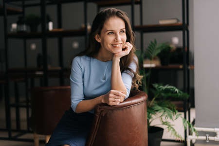 Smiling young businesswoman wearing stylish light blue dress sitting at the chair in office with modern interior, looking away. Portrait of charming business lady. Archivio Fotografico