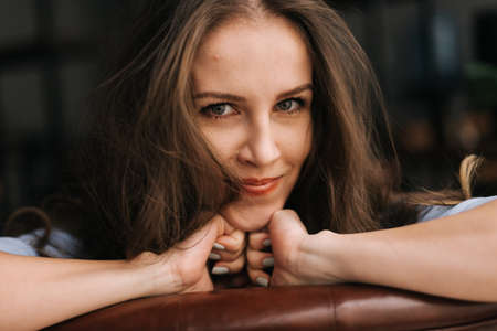 Close-up of face of sensual smiling young woman with long tousled hair sitting and leaning on the back of the chair. Charming business lady looking at camera, closeup.