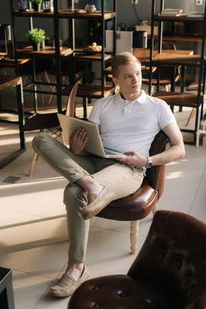 Confident young businessman wearing fashion casual clothing sitting on chair and holding laptop in his hand. Successful business man is working on laptop computer in trendy hipster start-up office.