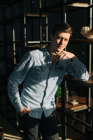 Handsome young man wearing fashion casual clothing standing near shelves in modern office room, looking at the camera, bright sunlight. Archivio Fotografico