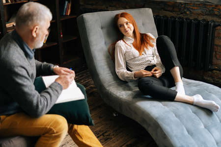 Professional senior man psychologist listening to patient and taking notes on clipboard during psychological consultation with upset female patient. . Concept of psychological treatment.