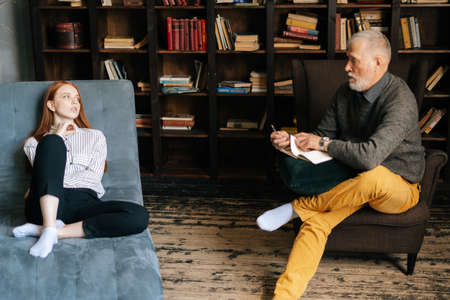 Successful mature man psychologist giving advices to patient at psychologist appointment. Frustrated red-haired young woman patient listening to older senior doctor explaining treatment