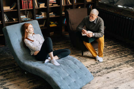 Attractive young woman with red hair lying on armchair talking about his problems with professional mature man psychotherapist or psychologist in cozy office room. Archivio Fotografico
