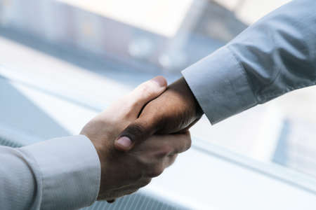 Close-up view of handshaking of unrecognisable two multiethnic colleagues businessman background of window. Concept of interracial friendship and cooperation.