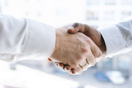 Close-up handshaking of two colleagues African business man and Caucasian businessman background of window, cityscape. Concept of interracial friendship and cooperation.