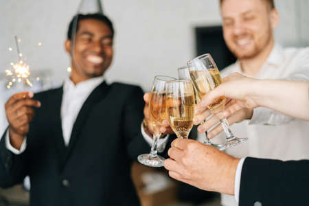 Close-up view of business team of multinational employees holding Bengal lights, clinking glasses of champagne and smiling cheerfully at corporate New Year or Happy Christmas eve.