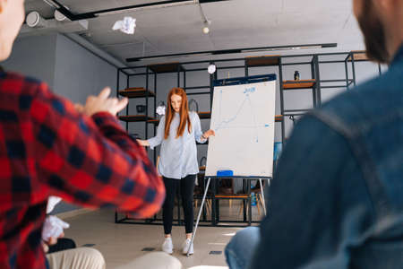 Low-angle shot of cheerful young business lady finishing presentation on whiteboard. Angered colleagues throw crumpled paper at frightened woman coworker. Confused businesswoman runs away and hides. Stok Fotoğraf