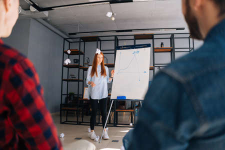 Dissatisfied colleagues throw crumpled paper balls at frightened woman coworker. Cheerful young business lady finishing report on white board. Confused female runs away and hides behind blackboard.