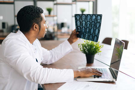 Side view of African American black male doctor in white coat analyzing history disease of patient using MRI brain head scan, working on laptop. Concept of medicine and health care.