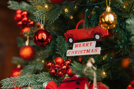 Close-up view of colorful Christmas decorations hanging on Christmas tree at eve of winter holidays. Concept of preparation home to new year holiday celebration.