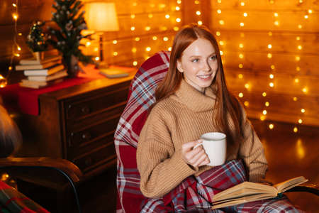 Happy young woman drinking hot coffee from cup and reading book while sitting at cosy rocking armchair with knitted plaid at cozy living room, background of wall decorated Christmas sparkling lights