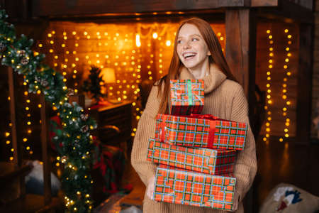 Portrait of cheerful young woman holding many beautiful Christmas gift boxes on background of xmas lights at cozy room, looking away. Happy lady received many presents for new year. Stockfoto