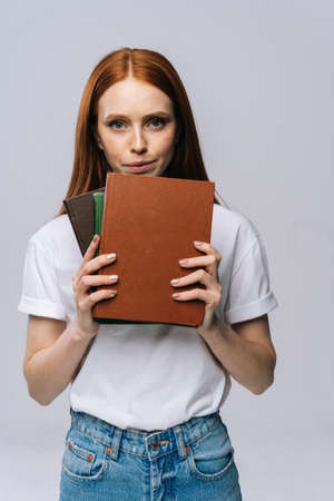 Upset sad young woman college student holding book and looking at camera on isolated gray background. Pretty redhead lady model wearing casual fashion clothes emotionally showing facial expressions. Reklamní fotografie