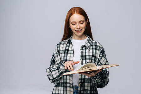 Smiling young woman college student turning pages of book while reading on gray isolated background. Pretty redhead lady model wearing casual clothes emotionally showing facial expressions.