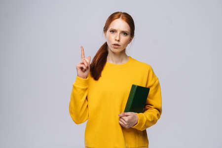 Serious young woman college student holding book and pointing finger up looking at camera on gray isolated background. Pretty redhead lady wearing yellow sweater emotionally showing facial expressions
