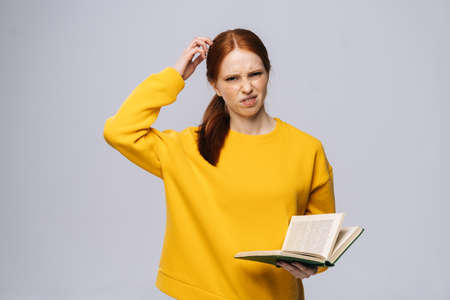 Doubtful dissatisfied young woman college student wearing yellow sweater looking at camera holding book on isolated gray background. Pretty redhead lady model emotionally showing facial expressions Reklamní fotografie