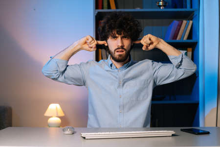 Front view of handsome bearded young man looking at camera covering ears with hands say blah blah do not wanna listening. Curly guy closing ears with hands and shaking his head.