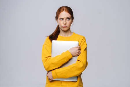 Frustrated upset young business woman or student holding laptop computer and looking away on isolated white background. Pretty lady model with red hair emotionally showing facial expressions.