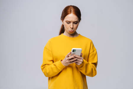 Displeased cute young woman reading bad news, feels dissatisfaction after receiving message on isolated white background. Pretty lady model with red hair emotionally showing facial expressions Foto de archivo