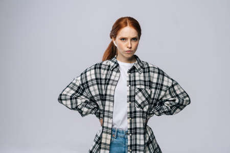 Serious red-haired young woman wearing wireless earphones looking at camera on isolated white background. Pretty redhead lady model emotionally showing facial expressions.