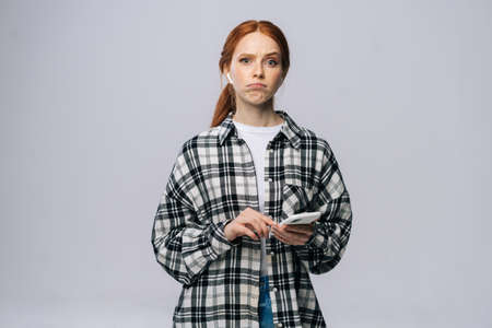 Doubtful red-haired young woman wearing wireless earphones typing online message on isolated white background, looking at camera. Pretty redhead lady model emotionally showing facial expressions.