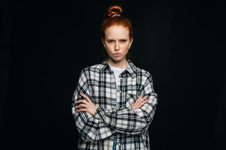Disgruntled red-haired young woman wearing wireless earphones with crossed hands looking at camera on isolated black background. Pretty redhead lady model emotionally showing facial expressions.