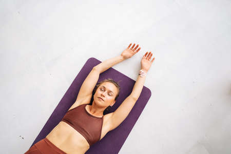 High-angle shot of fit young woman with perfect athletic body wearing sportswear working out lying on exercising mat. Concept of healthy lifestyle and physical activity at home.
