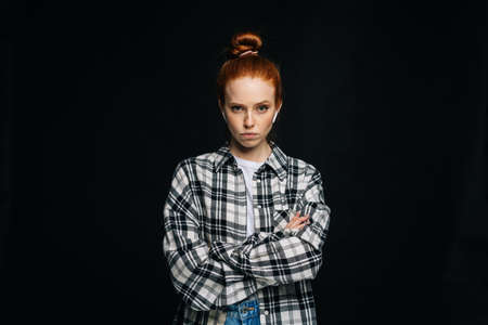 Angry red-haired young woman wearing wireless earphones with crossed hands looking at camera on isolated black background. Pretty redhead lady model emotionally showing facial expressions.